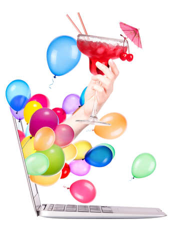 hand with glass of cocktail and balloons come out from a screen of a laptop computer isolated on white  photo