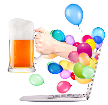 hand with glass of fresh beer and balloons come out from a screen of a laptop computer isolated on white background photo
