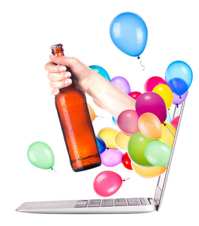 hand with bottle of fresh beer and balloons come out from a screen of a laptop computer isolated on white background photo