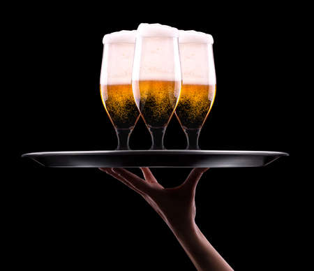 waiter hand and tray with Beer into glass on a black