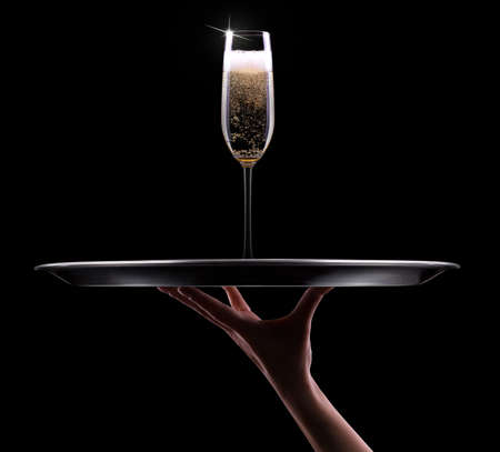 waiter hand with champagne on black background