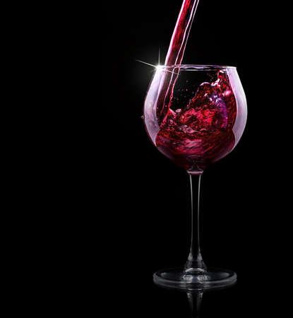 glass of red splashing wine on black  photo