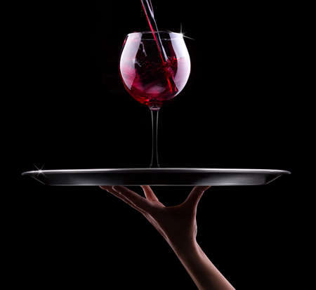 waiter hand and tray with glass of red wine on a black Stockfoto