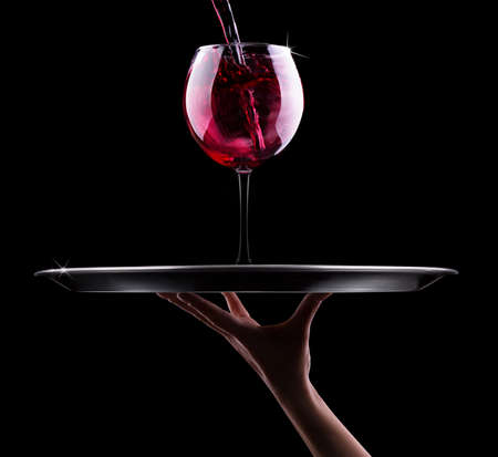 waiter hand and tray with glass of red wine on a black photo