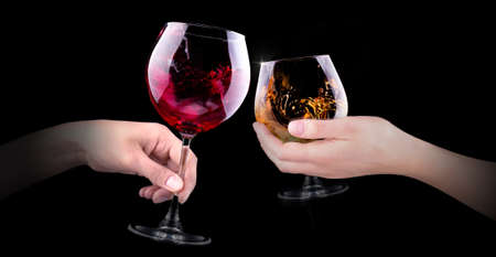 hand making toast with glass of red splashing wine and brandy on black background photo