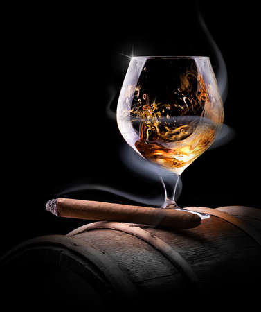 old bar: Cognac glass shrouded in a smoke on a black background