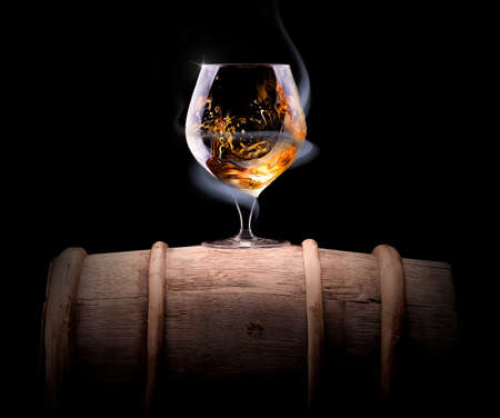 Cognac glass shrouded in a smoke on a black background photo