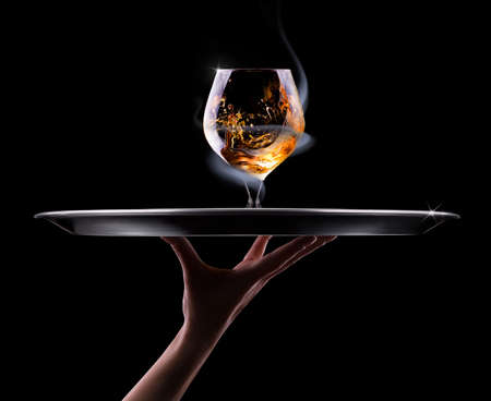 waiter hand and tray with Cognac or brandy on a  black background photo