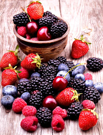 나무 테이블에 맛있는 여름 과일. 체리, 블루 베리, 딸기, 나무 딸기, 블랙 베리, 석류