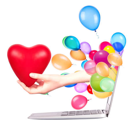 hand with a heart - gift come out from a screen of a laptop computer with balloons photo