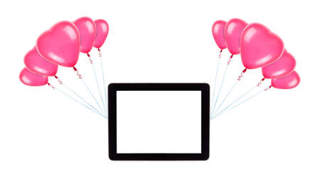tablet computer with empty touch screen hanging on color balloons rising high photo