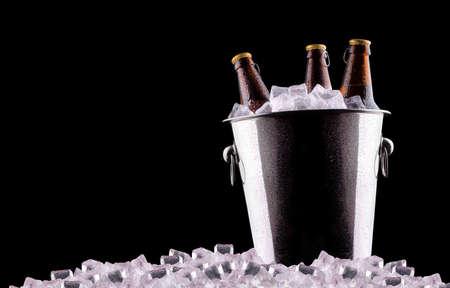 Beer bottles in ice bucket isolated on black photo