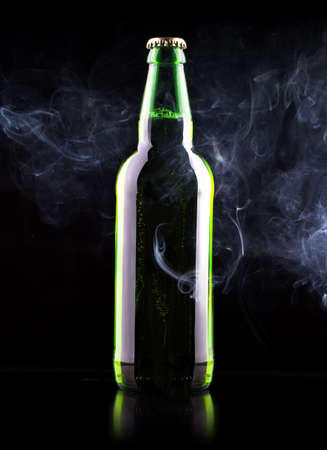 wet Beer bottle with chill smoke on a black photo