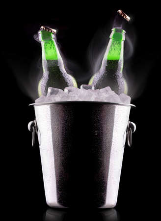 Beer bottles in ice bucket isolated on black photo