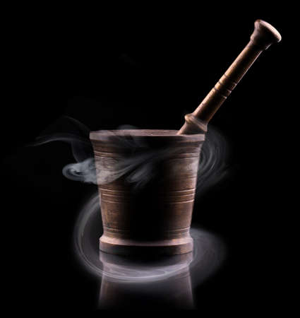 Old mortar with pestle and smoke on black backround photo