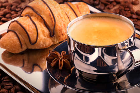 coffeetime: breakfast coffee cup with chocolate croissant. Vintage background