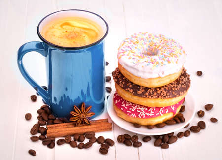 Tasty donut with a cup of coffee on a white table photo