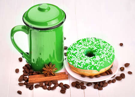 Tasty donut with a cup of coffee and sugar on a white wooden table photo