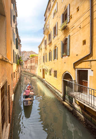 Gondola with gondolier in Venice channel, Italy photo