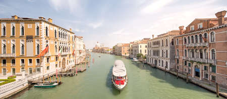 barbaro: View of the Basilica of Saint Mary of Health (Basilica di Santa Maria della Salute), with vaporetto and boats on grand canal in Venice under Ponte dellAccademia, Italy
