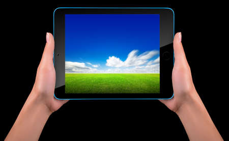 Tablet computer with blue sky and green grass  photo