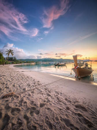 Beautiful image of sunset with colorful sky and Longtail boat on the sea tropical beach. Thailand photo