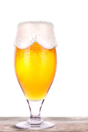 unbottled: Frosty glass of light beer on a wooden table isolated on a white background