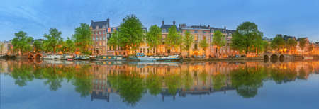 amstel: Panoramic view and cityscape of Amsterdam with boats, old buildings and Amstel river, Holland, Netherlands.
