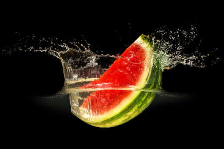 Fresh melon falling in water with splash on black background. Stock Photo