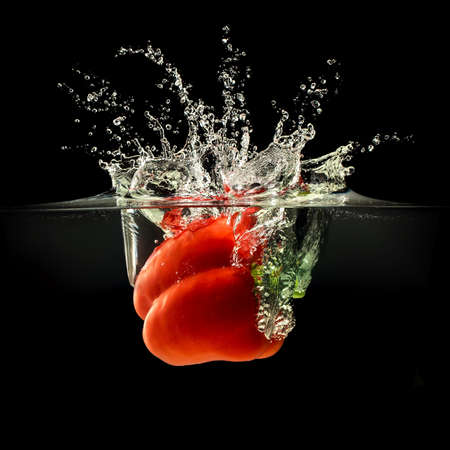 Red bell pepper falling in water with splash on black background. Stock Photo