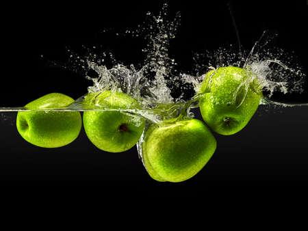 Gruppe von grünen Äpfeln in Wasser mit Spritzen auf schwarzem Hintergrund fallen.