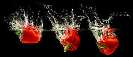 Rote Paprika fällt in Wasser Standard-Bild