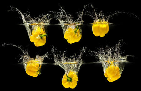 Yellow bell pepper falling in water