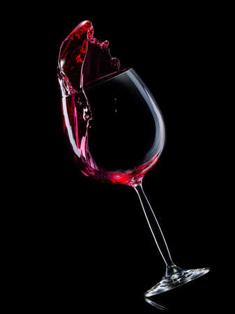 Glass for red wine with splashes isolated on black background. Stock Photo