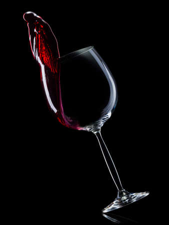 Glass for red wine with splashes isolated on black