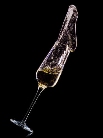 Glass for champagne with bubbles and splashes isolated on black 写真素材