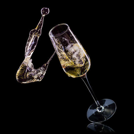 Glass for champagne with bubbles and splashes isolated on black