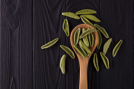 Top view of foglie spinach pasta on wooden table with spoon isolated on black Stock fotó