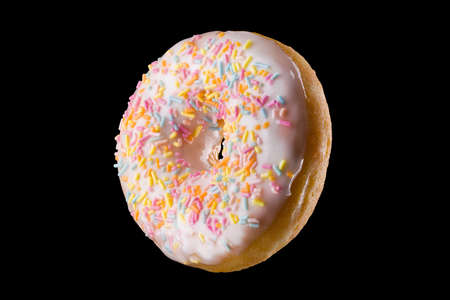 Glazed donut with sprinkles on a black