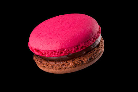 French chocolate macaroon or macaron isolated on black