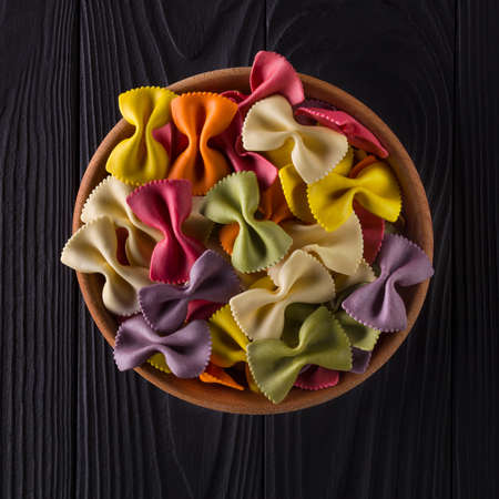 Top view of colorful farfalle pasta in bowl on black wooden table