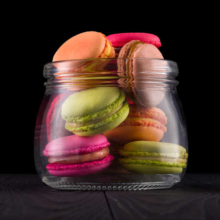 Jar of french colorful macaroon or macaron on wooden table isolated on black Stockfoto