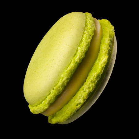Macro photo of french green tea macaroon or macaron isolated on black background