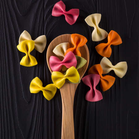 Top view of colorful farfalle pasta on black wooden table with spoon