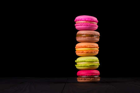 Stack of french colorful macaroons on wooden table isolated on black