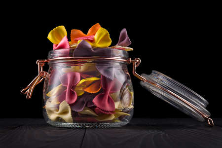 Jar of colorful farfalle pasta on wooden table isolated on black