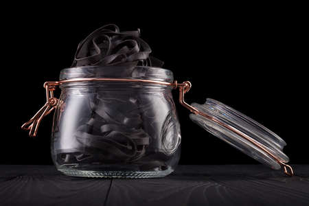 Jar of tagliatelle pasta nests on wooden table isolated on black background