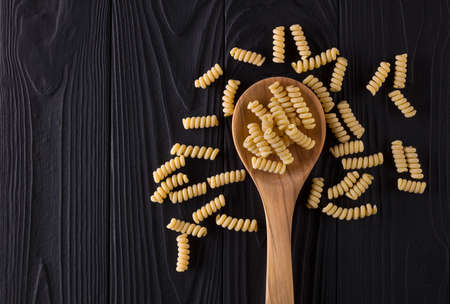 Top view of fusilli pasta on black wooden table with spoon