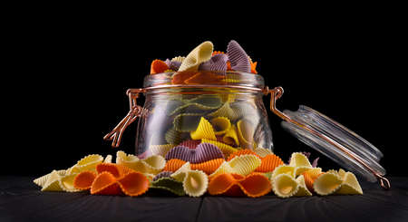 Jar of colorful farfalle pasta on wooden table isolated on black background Stock fotó