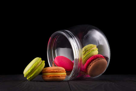 Jar of french colorful macaroon or macaron on wooden table isolated on black Stock fotó